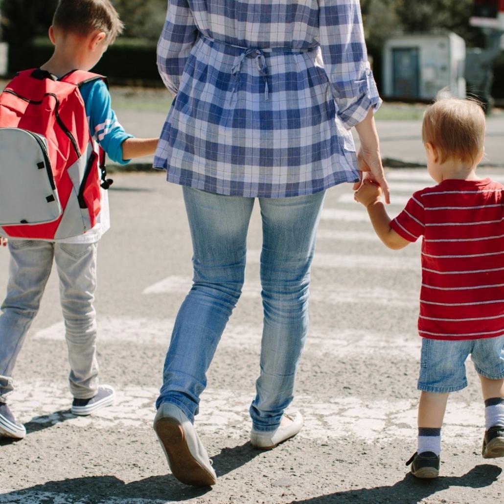 Mama z synami przechodzi przez pasy